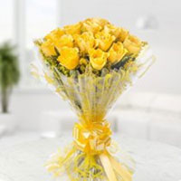 15 vibrant yellow roses surrounded by lemonium, wrapped in fancy cellophane paper