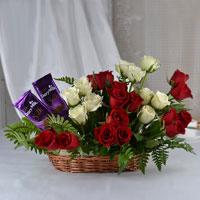25 Red & White Roses arrangement in a basket, 2 Cadbury dairy milk silk chocolate (Weight: 60 gm)